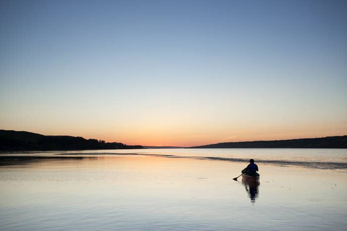 A photo of a person canoeing on a lake during sunset