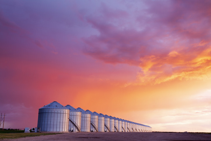 A line of steel silos with a bright pink and orange sunset behind them