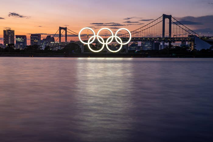 The Olympic rings lit on the side of a bridge