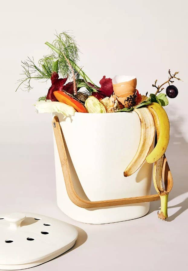 A cream, organic compost bin with a vented lid and bamboo handle filled with compost-friendly foods