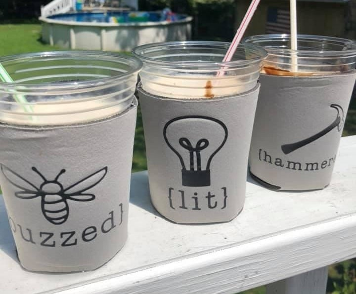 Reviewer photo of grey coozies with the words buzzed, lit, and hammered on each one with corresponding art of a bee, a lightbulb, and a hammer