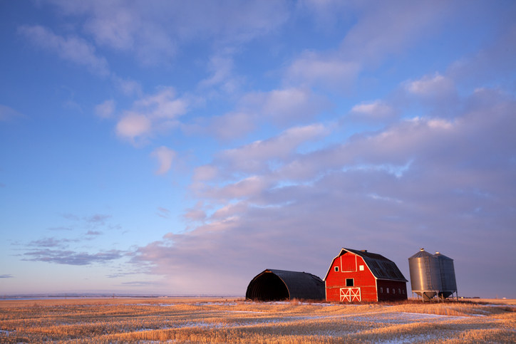 A photo of a red barn and steel silos in an open grain field