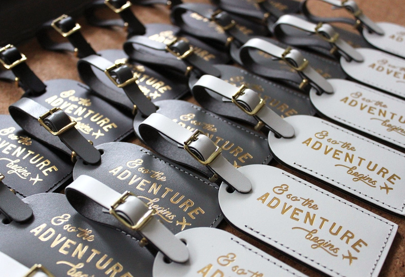 """Black and white luggage tags that say """"and so the adventure begins"""""""