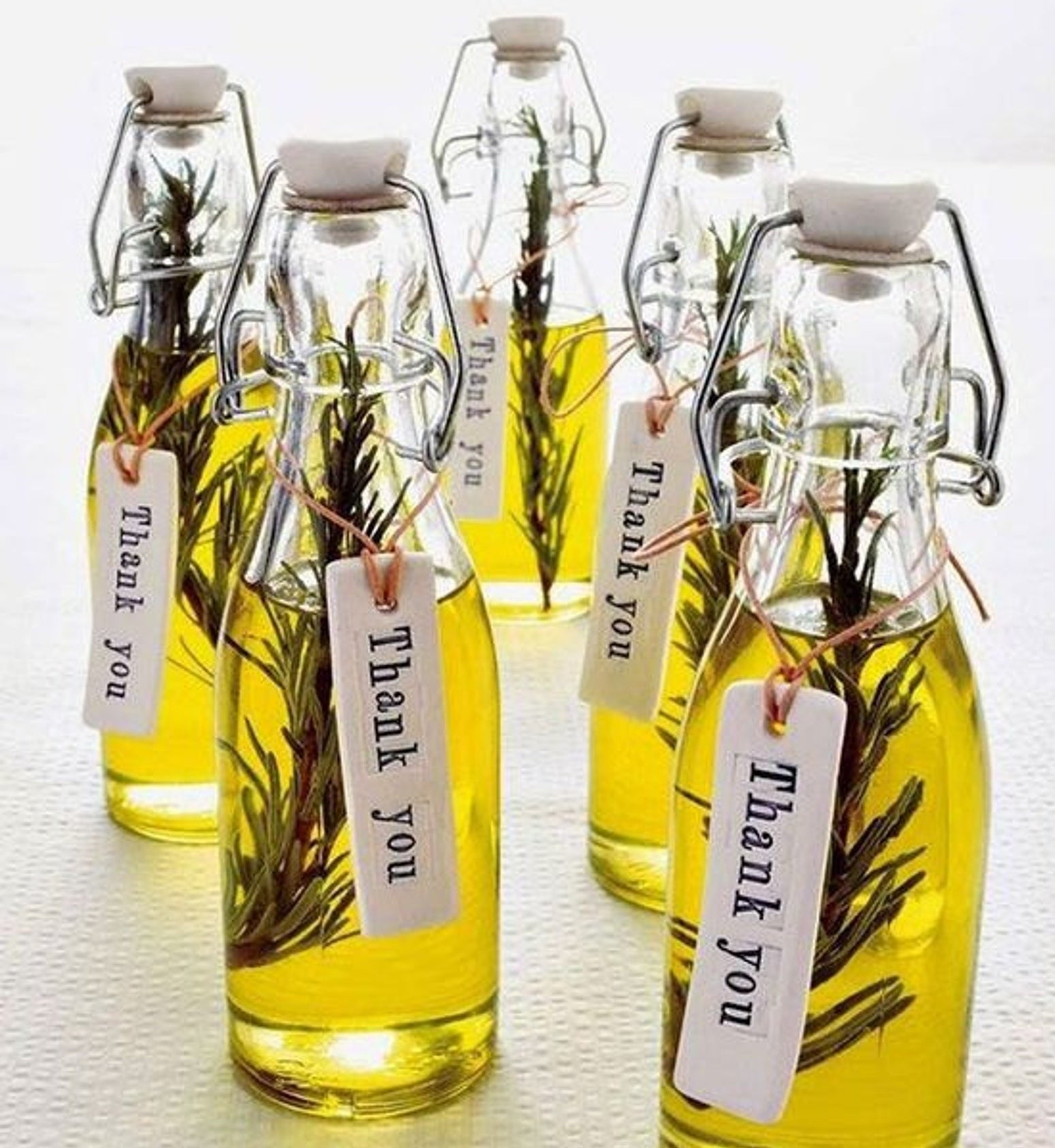 """The olive oil in bottles with a tag around the neck that says """"Thank you"""""""