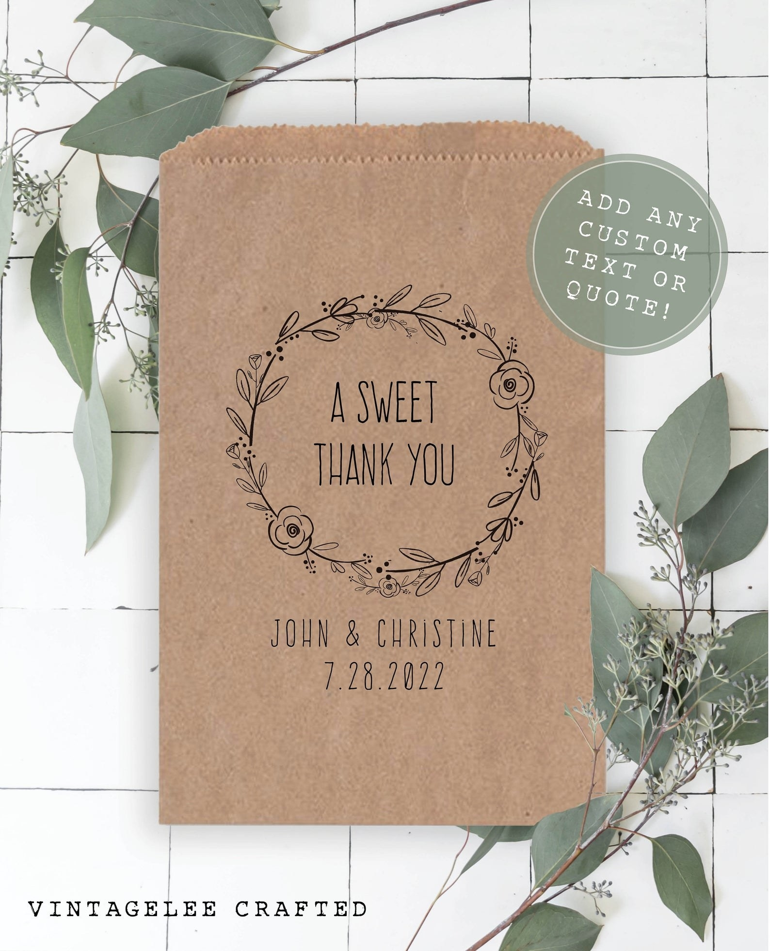 """A brown paper baked goods bag with a garland design and the words """"A sweet thank you"""" inside it and below that it says """"John and Christine"""" with a date"""