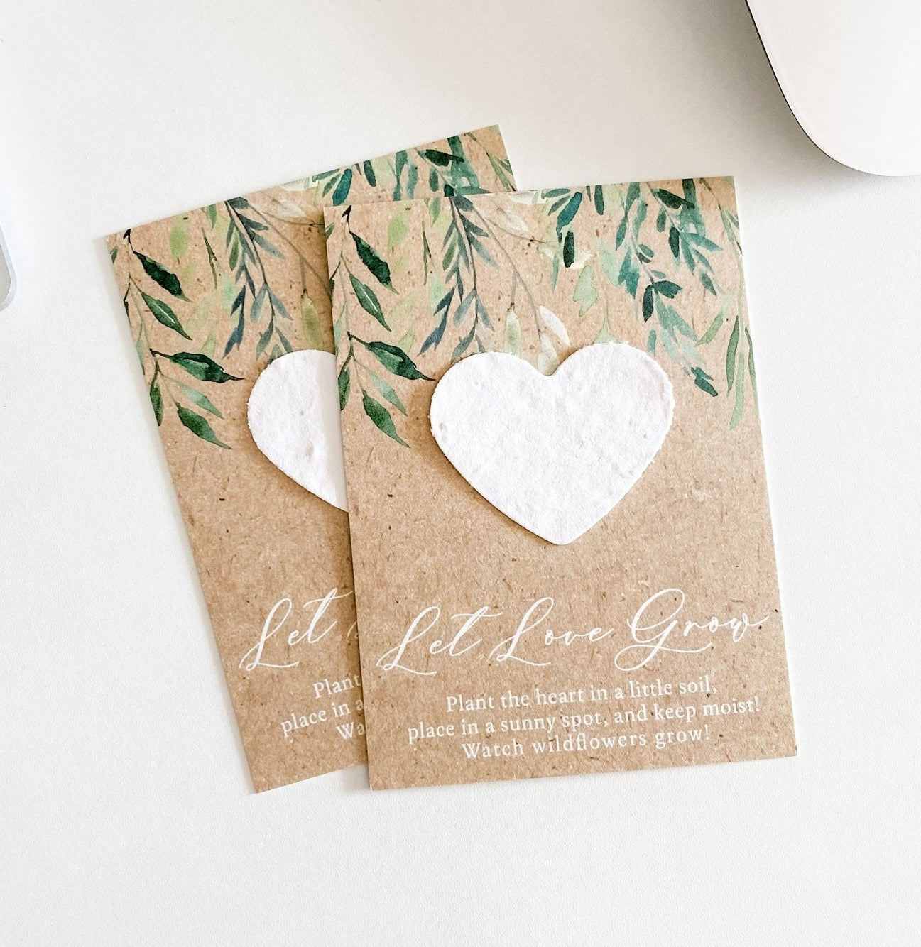 """Two natural cards with a heart shaped seed paper and says """"Let love grow, plant the heart in a little soil, place in a sunny spot, and keep moist, watch wildflowers grow"""""""