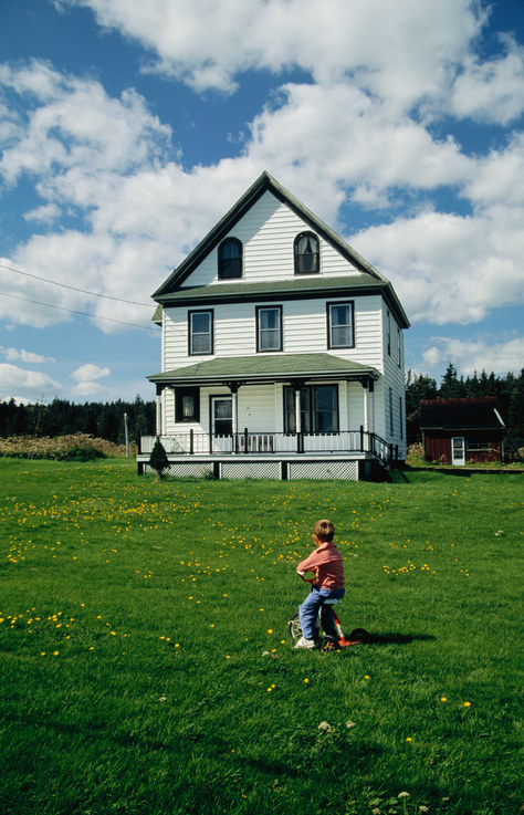 A photo of a young boy on a tricycle staring up at a white farmhouse from the front lawn