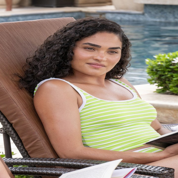 Brittany O'Grady reads in a lounge chair poolside