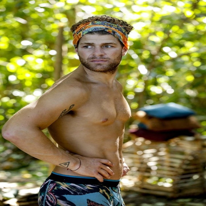 Alec Merlino stands shirtless in the jungle on SURVIVOR
