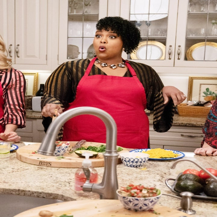 Natasha Rothwell stands in a kitchen wearing a red apron in LIKE A BOSS