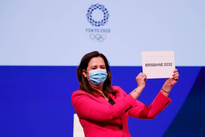 PremierAnnastacia Palaszczuk holds up a sign saying Brisbane 2032