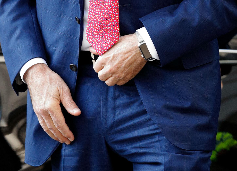 A man in a suit wearing an Apple Watch