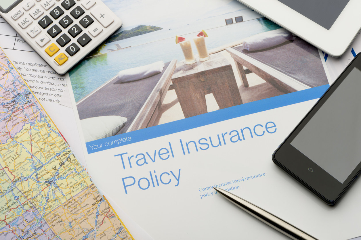 A travel insurance policy paper, a calculator, map, and phone spread out on a table
