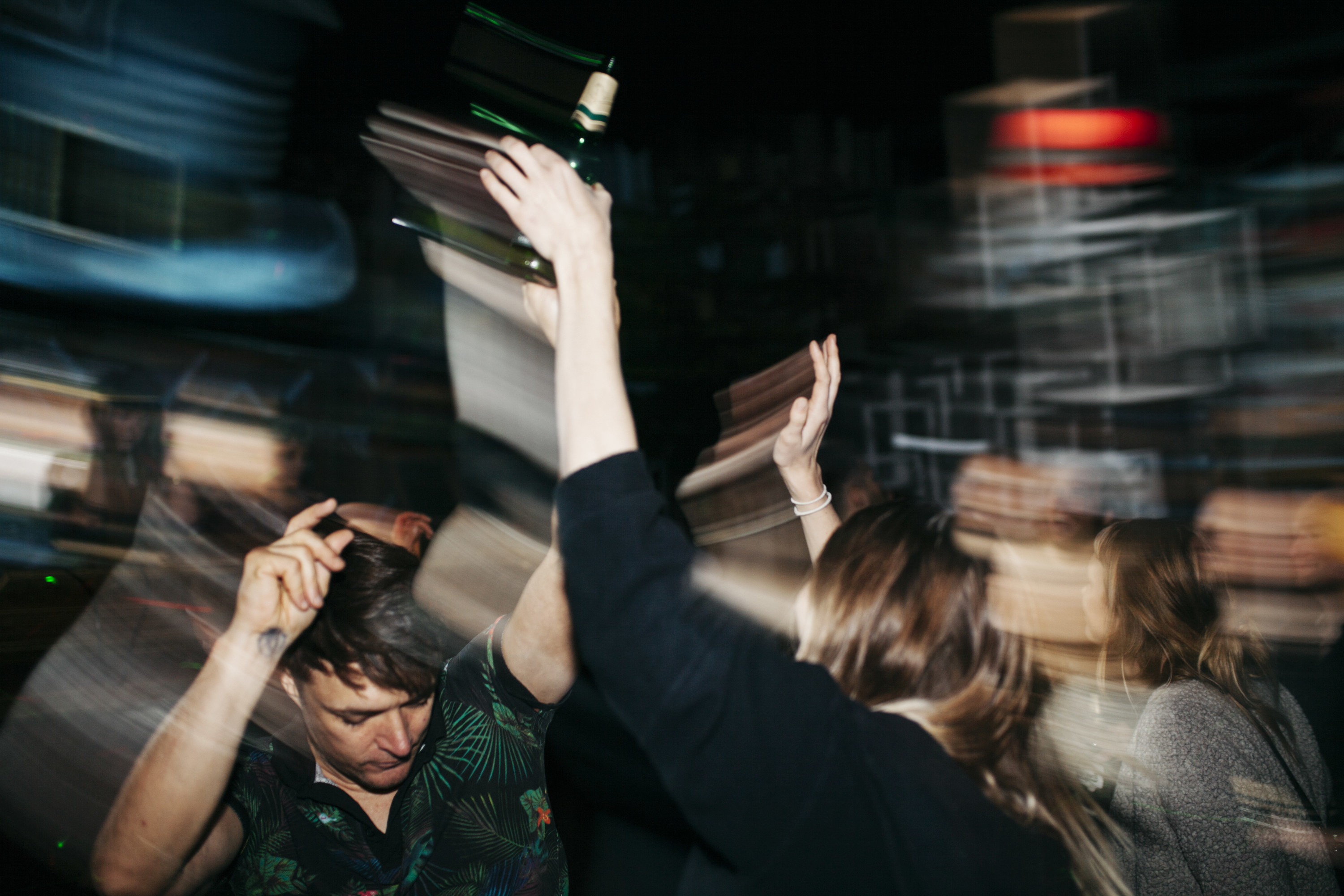 A blurry photo of people dancing at a party in the dark