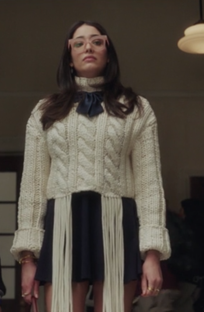Luna wears a dark, high-waisted ruffle skirt and a knit sweater with fringe on the hem