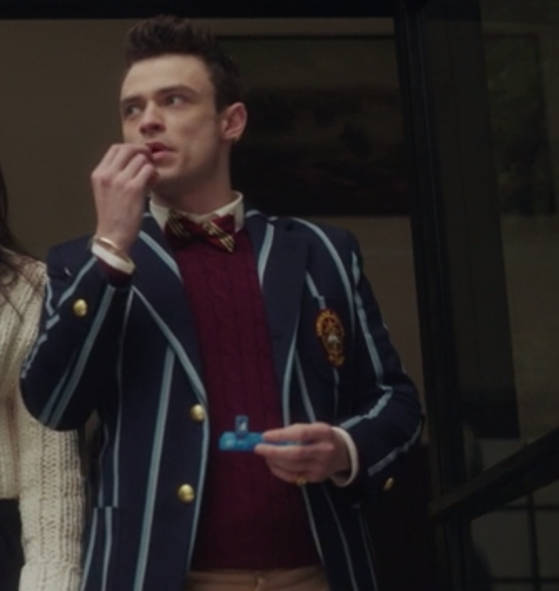 Max wears his pin-striped uniform blazer over a knit sweater and a bow tie that matches the sweater