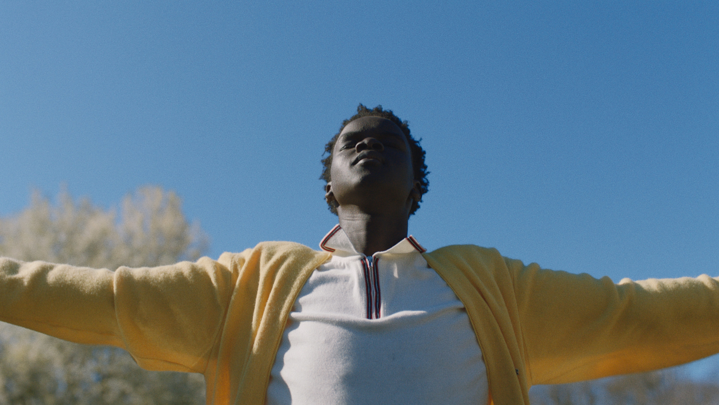 A young man with arms spread wide raises his face to the sun with his eyes closed