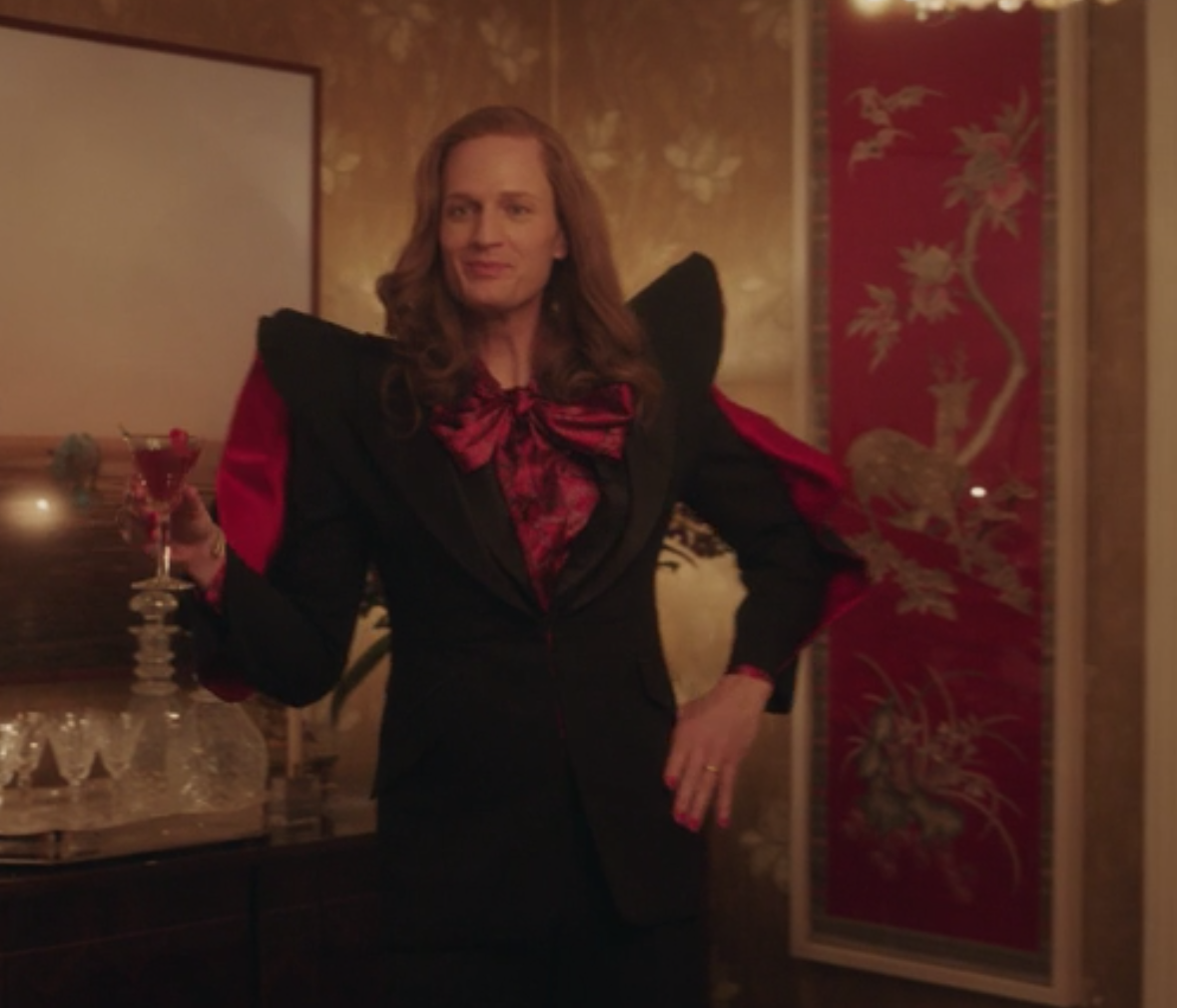 Gideon wears a black fitted blazer with oversize shoulder pads and matching bow tie