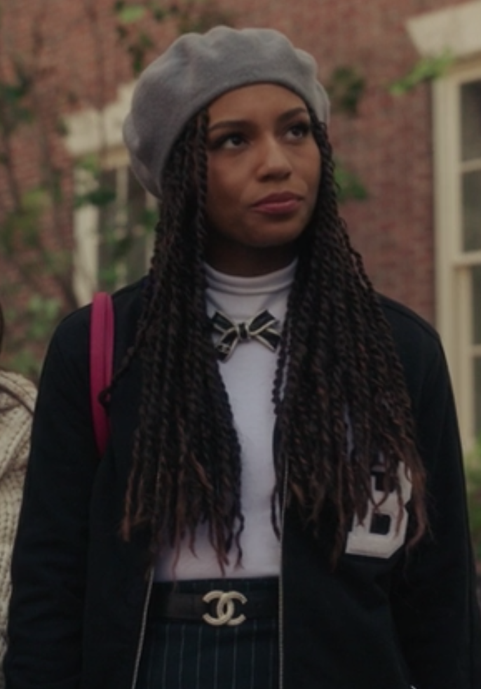 Monet wears a high-waisted pin-striped skirt with a T-shirt tucked into it under a dark letterman jacket and a beret