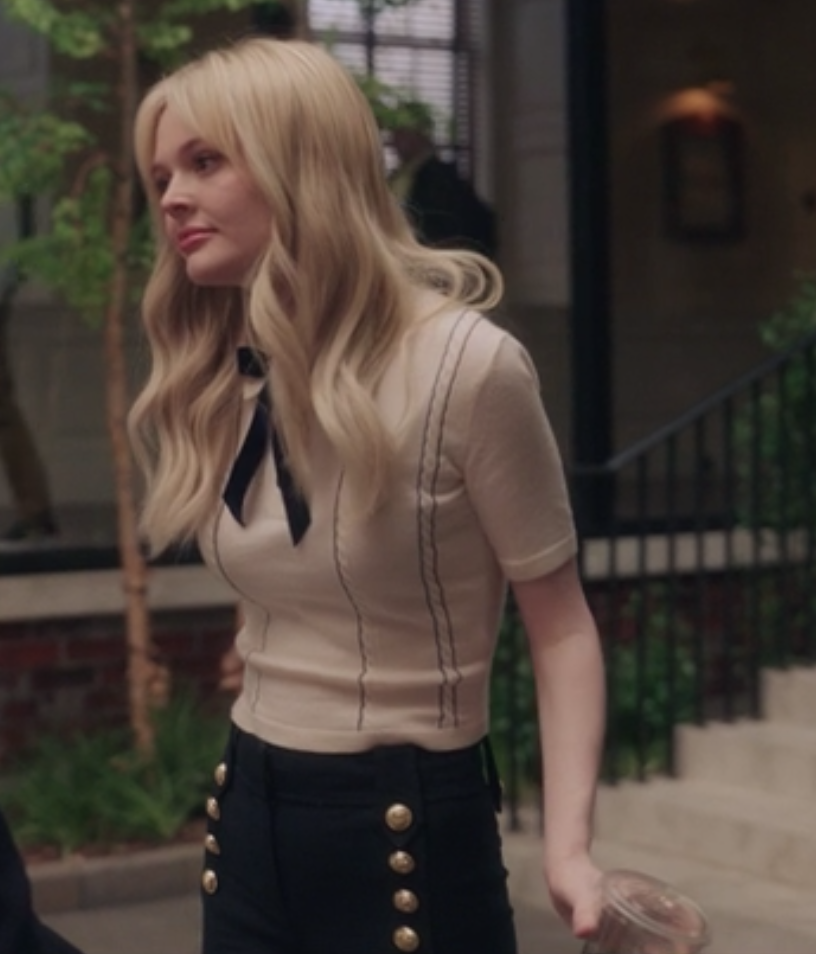 Audrey wears a knit sweater, oversize bow tie, and high-waisted pants with brass buttons on it