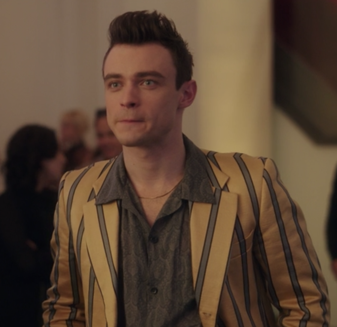 Max wears a tight-fitting pin-striped blazer over a paisley patterned button-up shirt