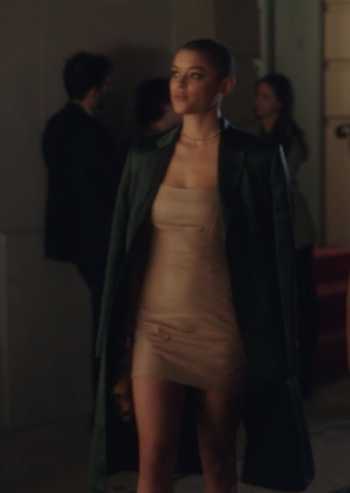 Julien wears a long dark trench coat over a tight-fitting minidress