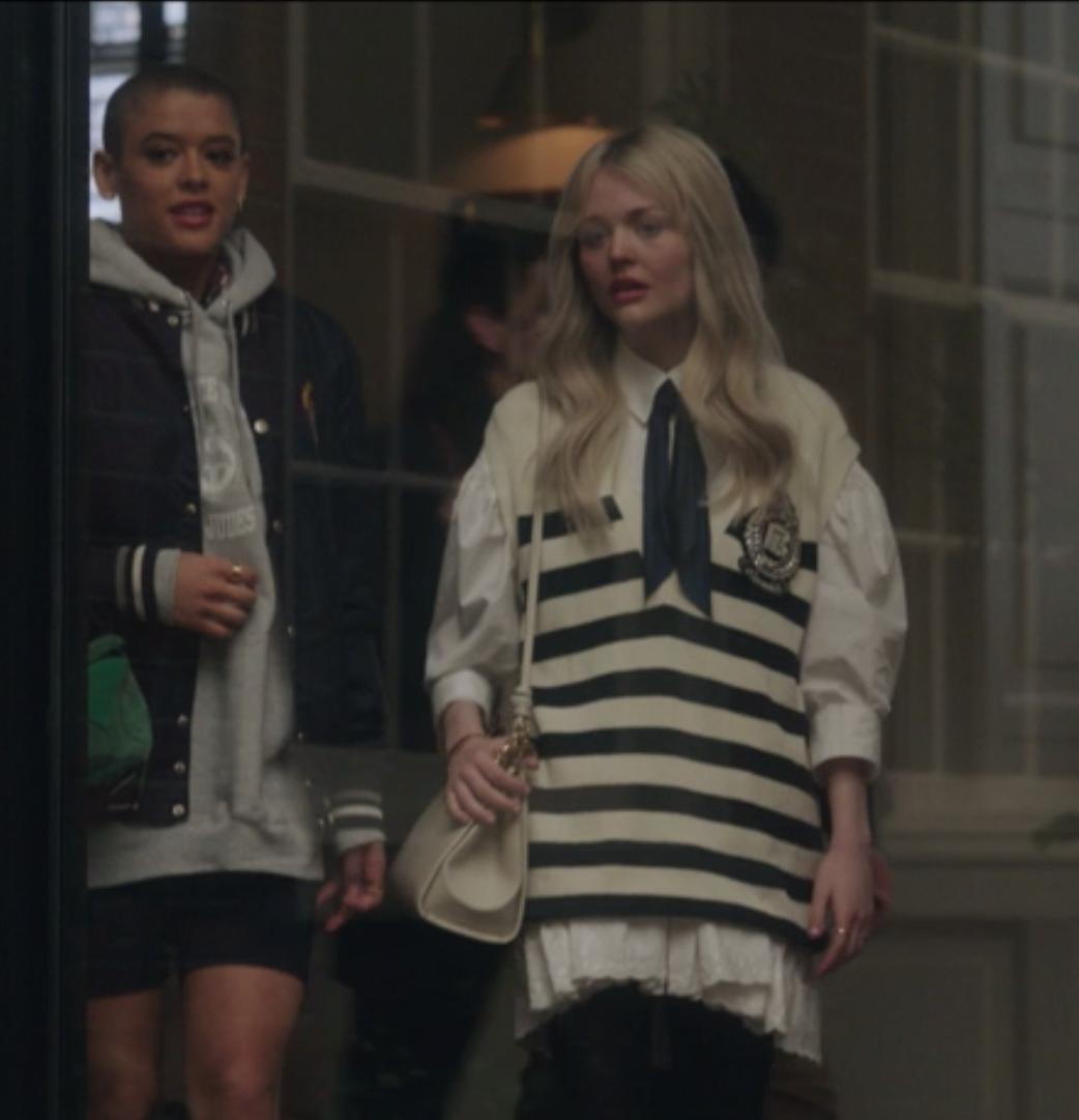 Julien wears biker shorts and an oversize hooded sweatshirt under a letterman jacket. Audrey wears a striped vest over a white lace long-sleeved shirt