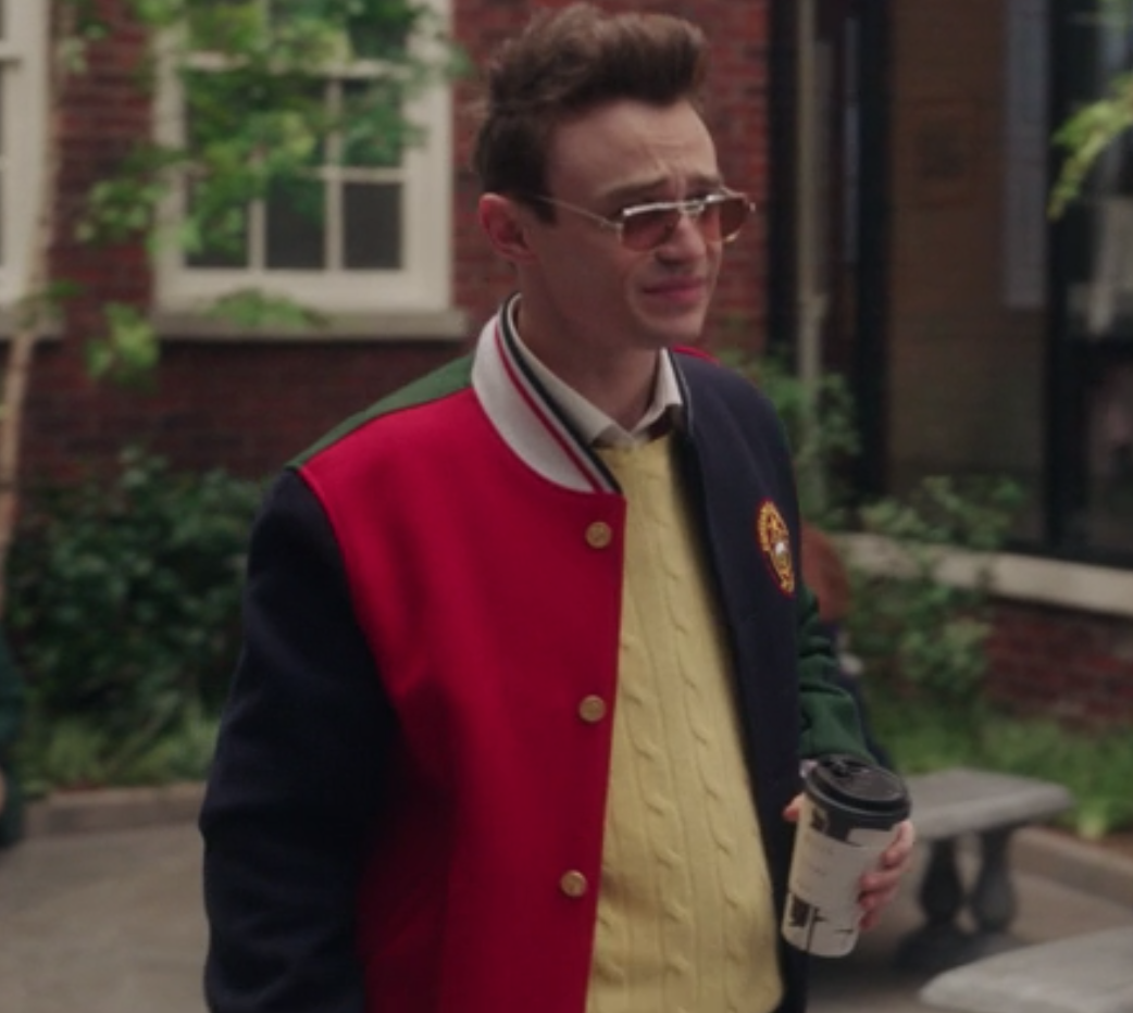 Max wears a colorblock letterman jacket over a knit sweater