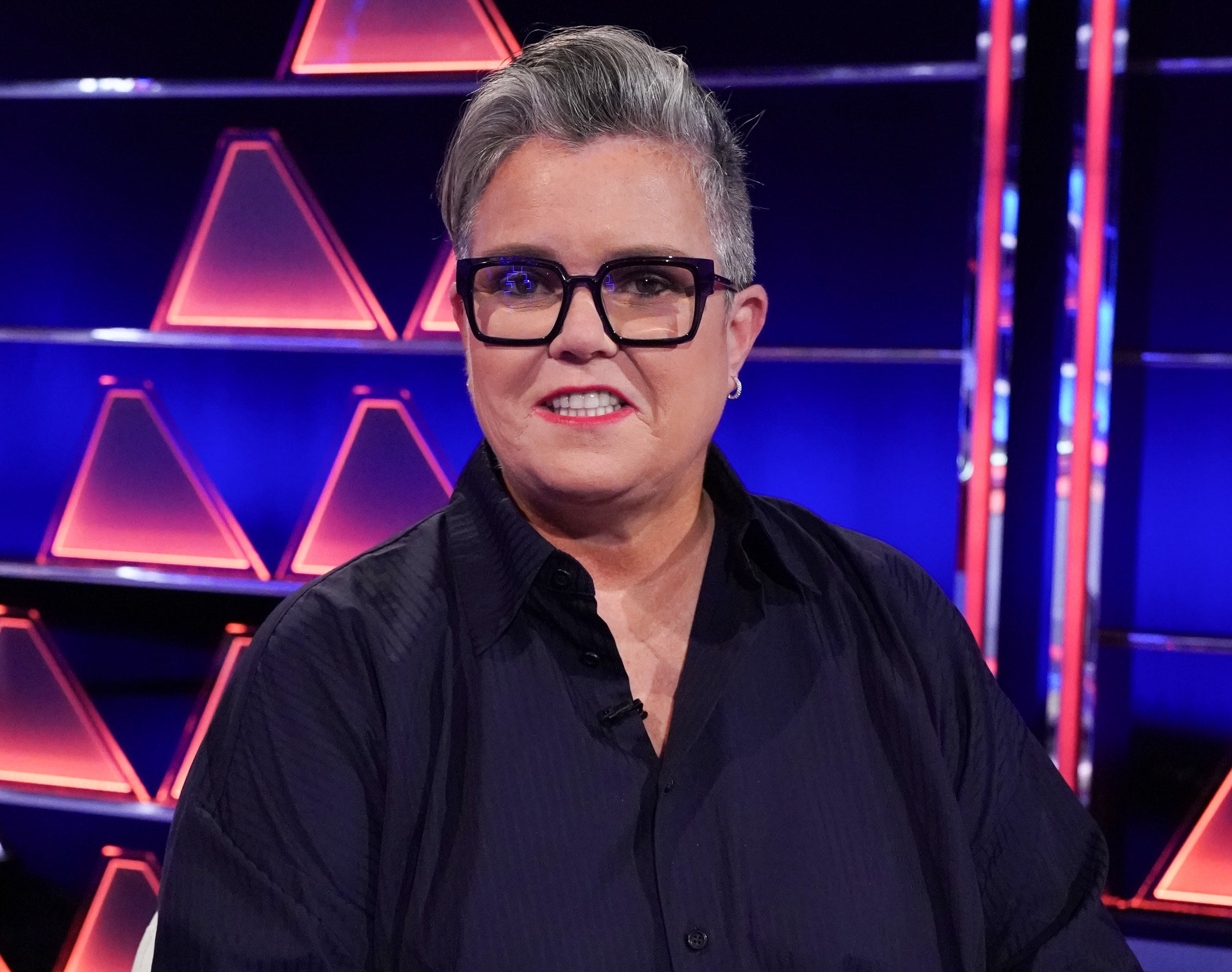 Rosie wears a black button down while smiling on the set of a game show