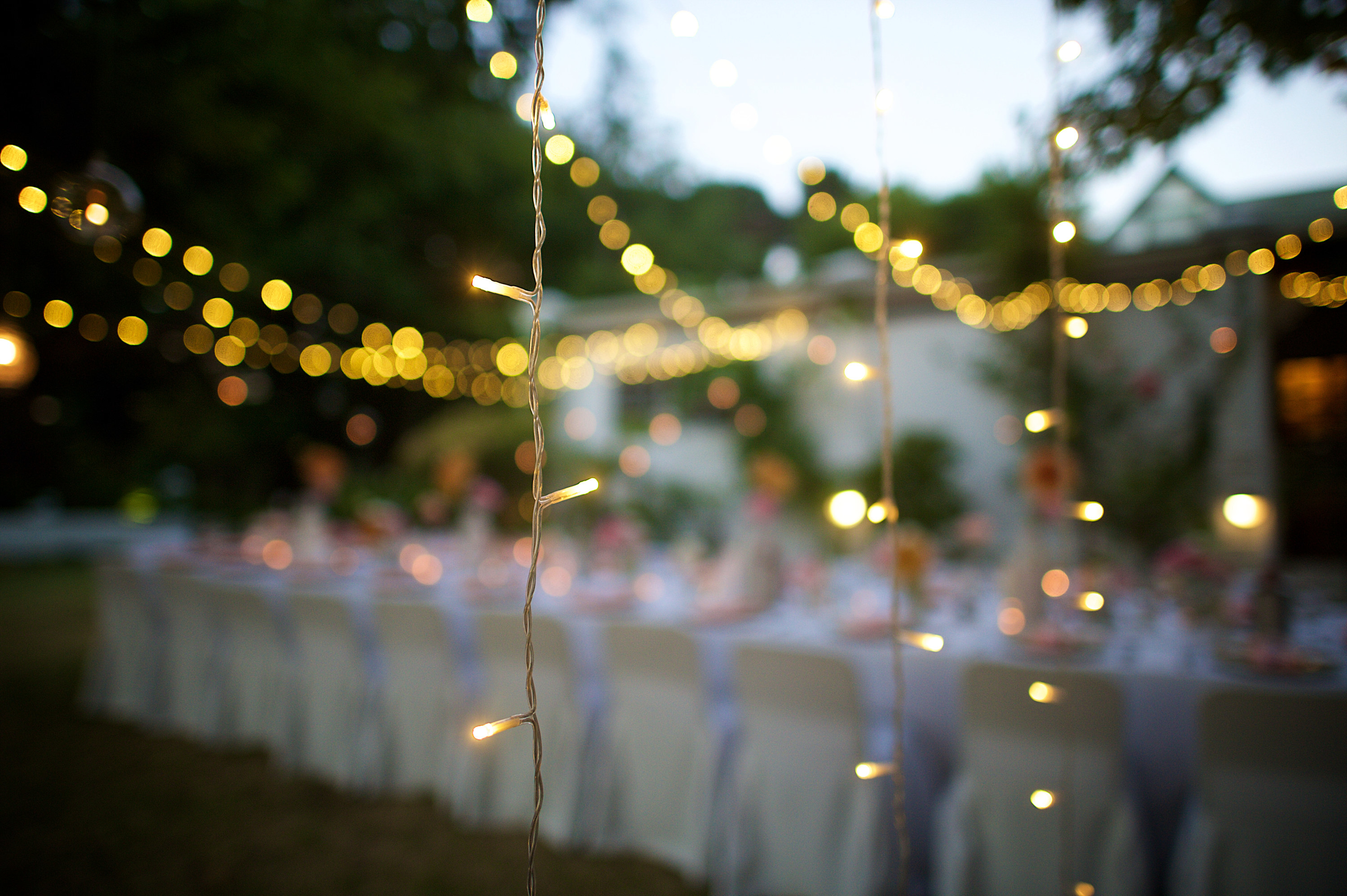 A blurry photo of a wedding table with fairy lights strung over it