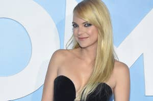 Anna Faris poses at a red carpet event while wearing a dress