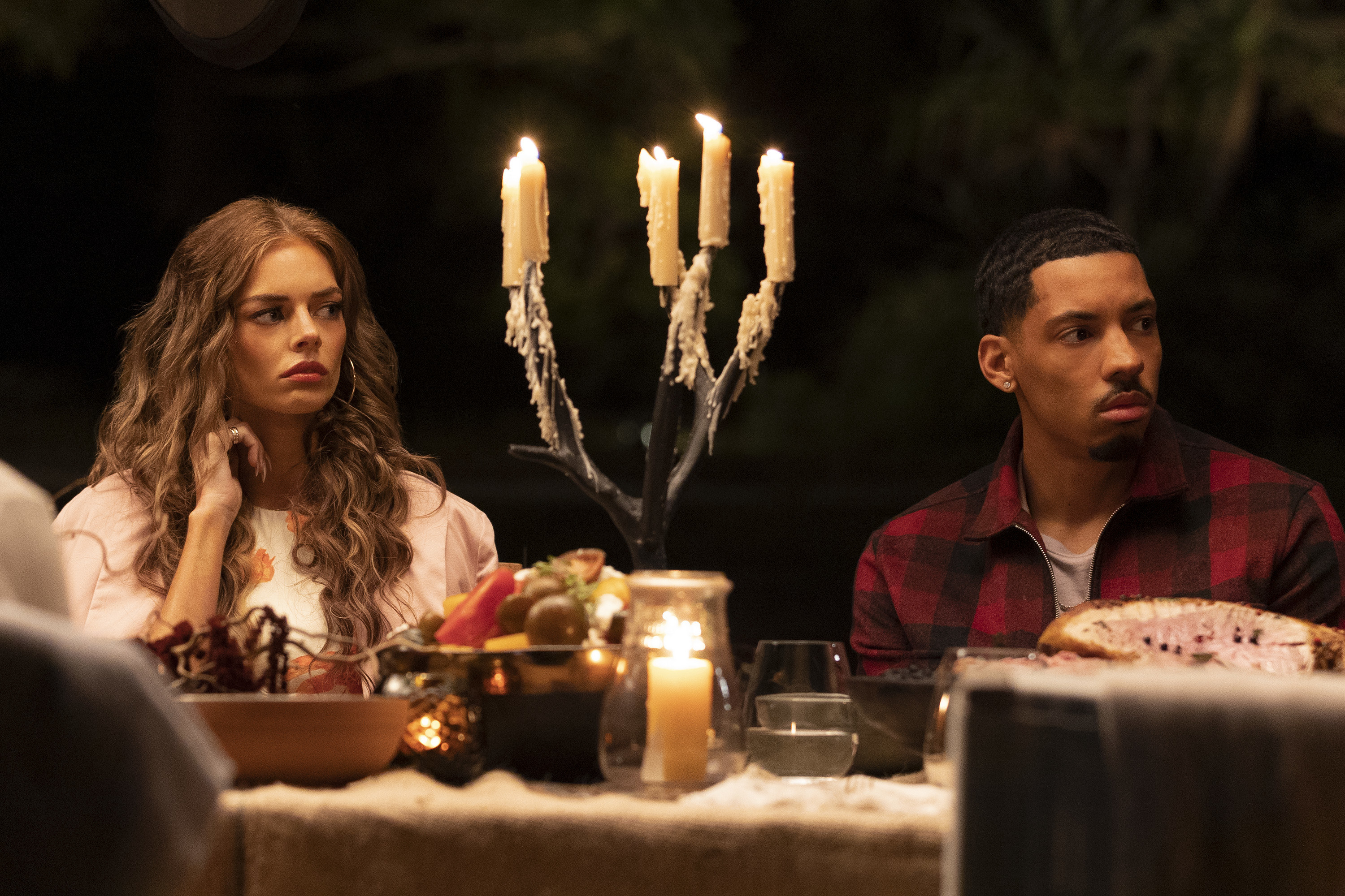 A close up of two characters sitting down at a candle-lit dinner table; they look worried