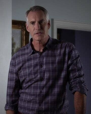 Kenneth DiLaurentis leans a bit to the side as he stands in the living room of his house