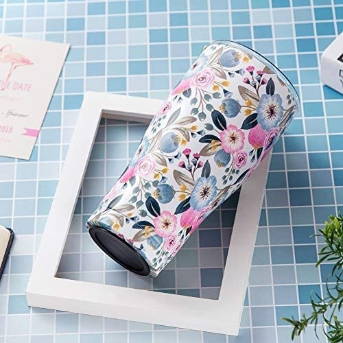 a floral tumbler on a tiled table