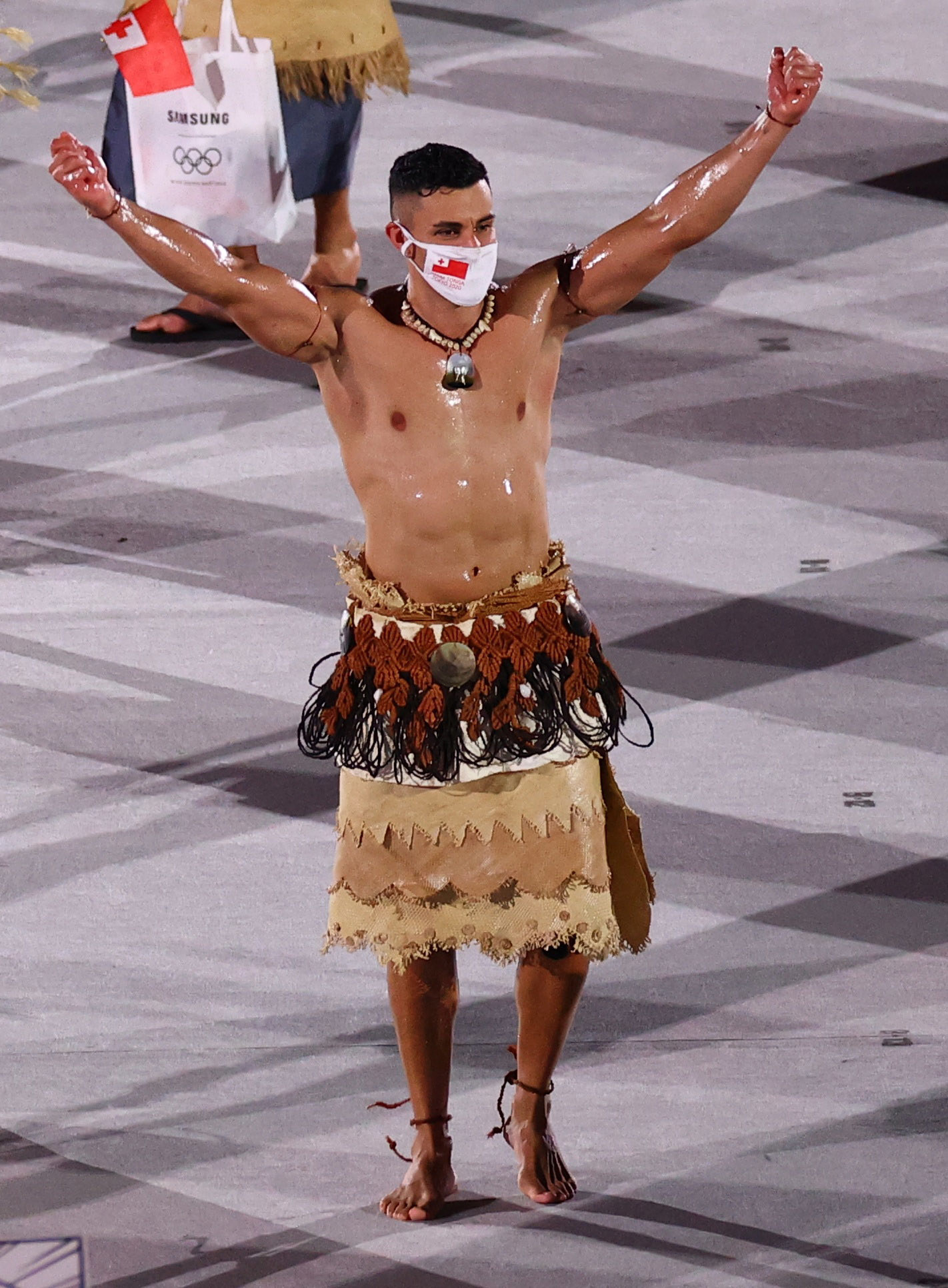 Pita Taufatofua is seen with an oily, muscled chest as he marches through an empty stadium carrying Tonga's flag next to his fellow athletes