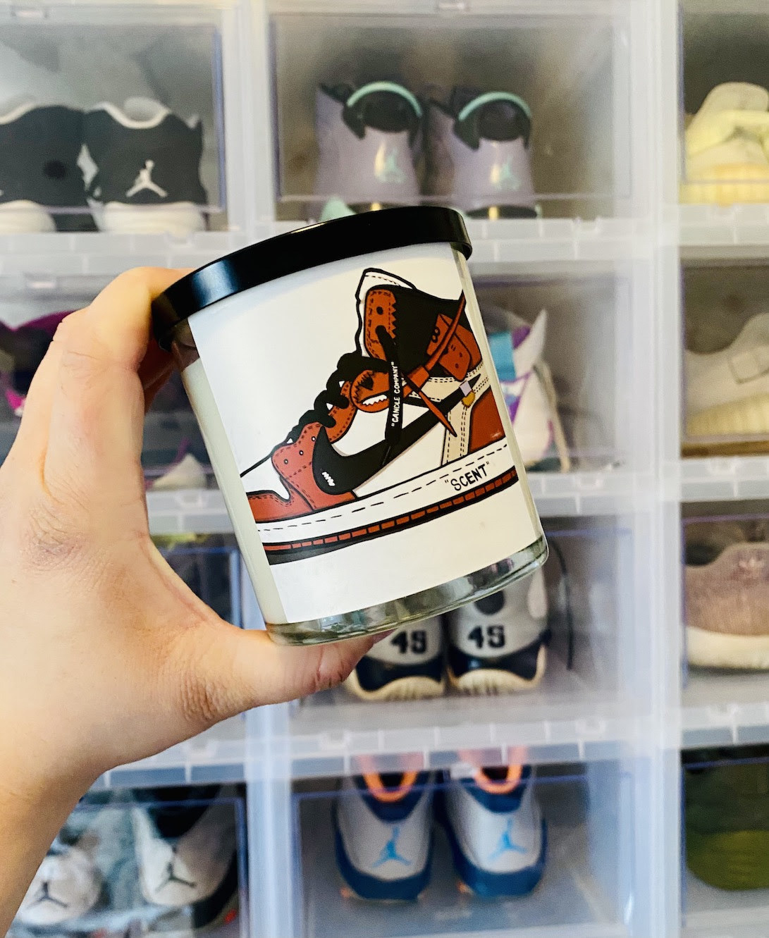buzzfeed editor holding a candle jar with an illustration of a black, white, and red Air Jordan 1 sneaker on it