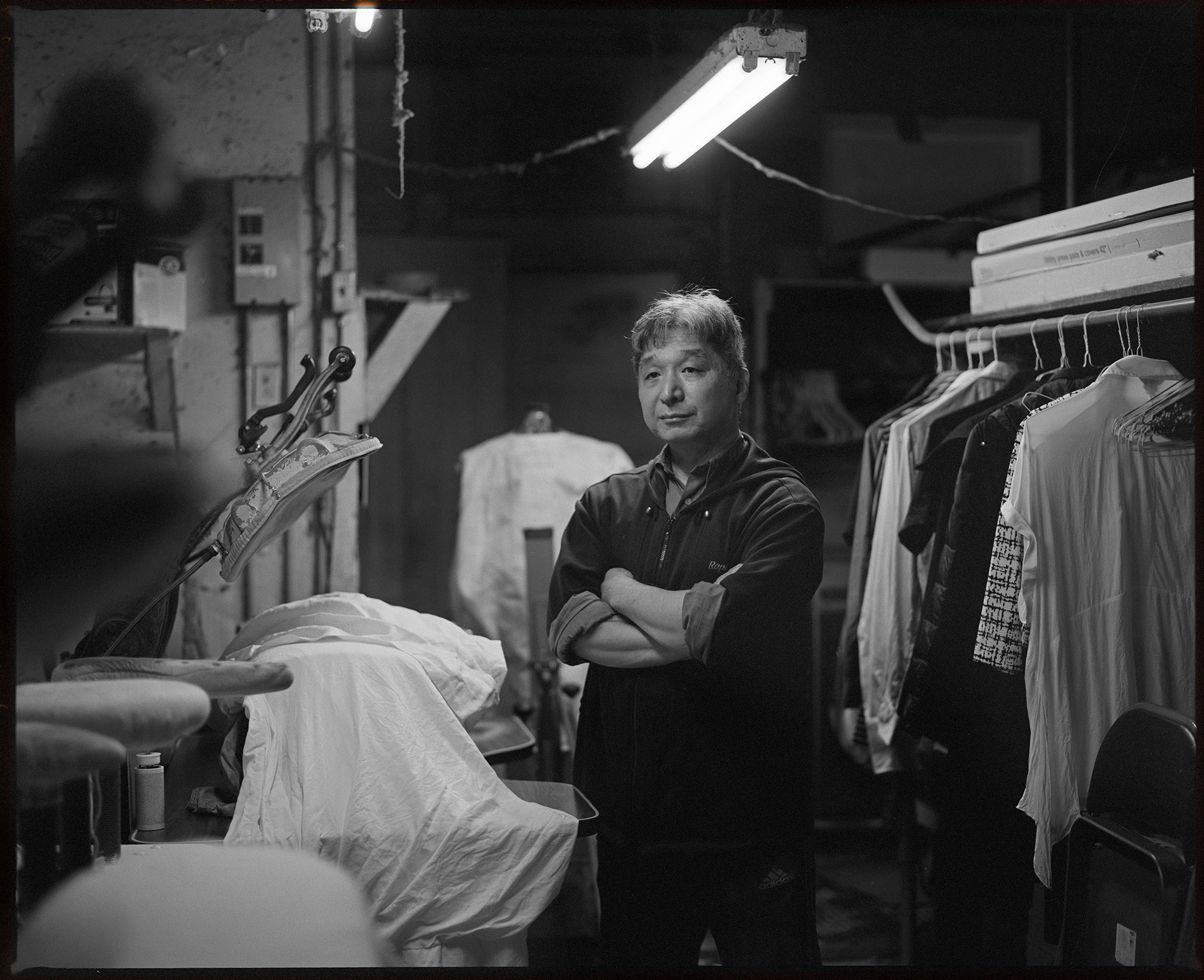 A man stands with his arms crossed in front of laundry machines under a fluorescent light