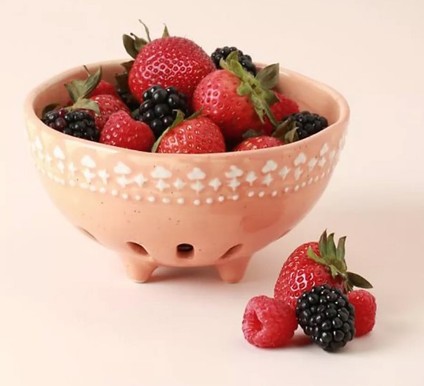 An orange, ceramic berry basket filled with mixed berries