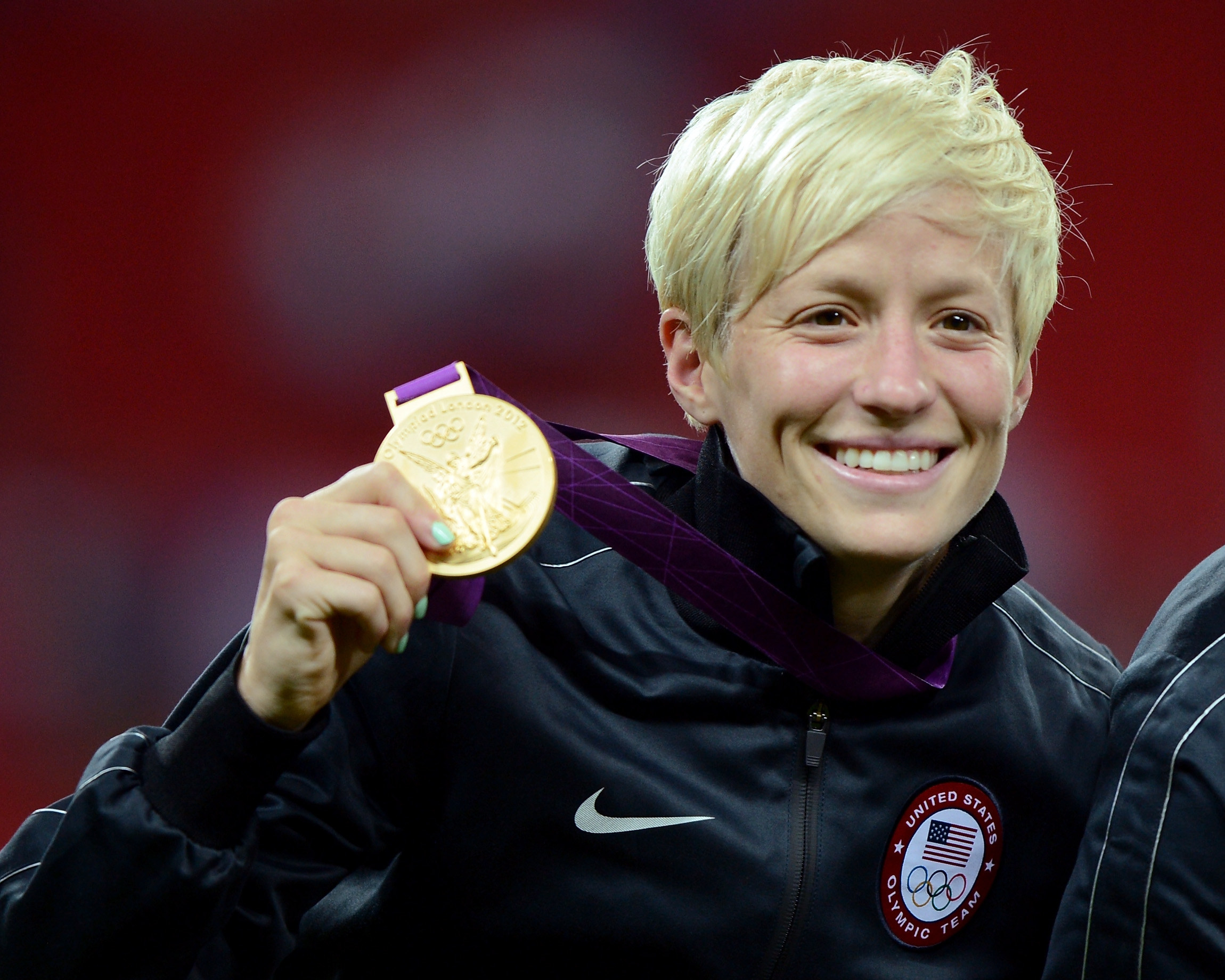 Rapinoe smiling while holding a gold medal