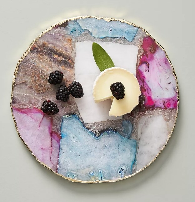 A round, multi-colored, agate cheese board with a gold rim