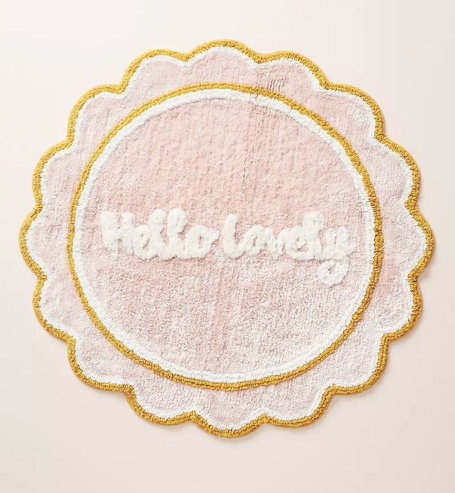 """A peach bath mat with scalloped edging that says """"Hello lovely"""" in white cursive in the center"""