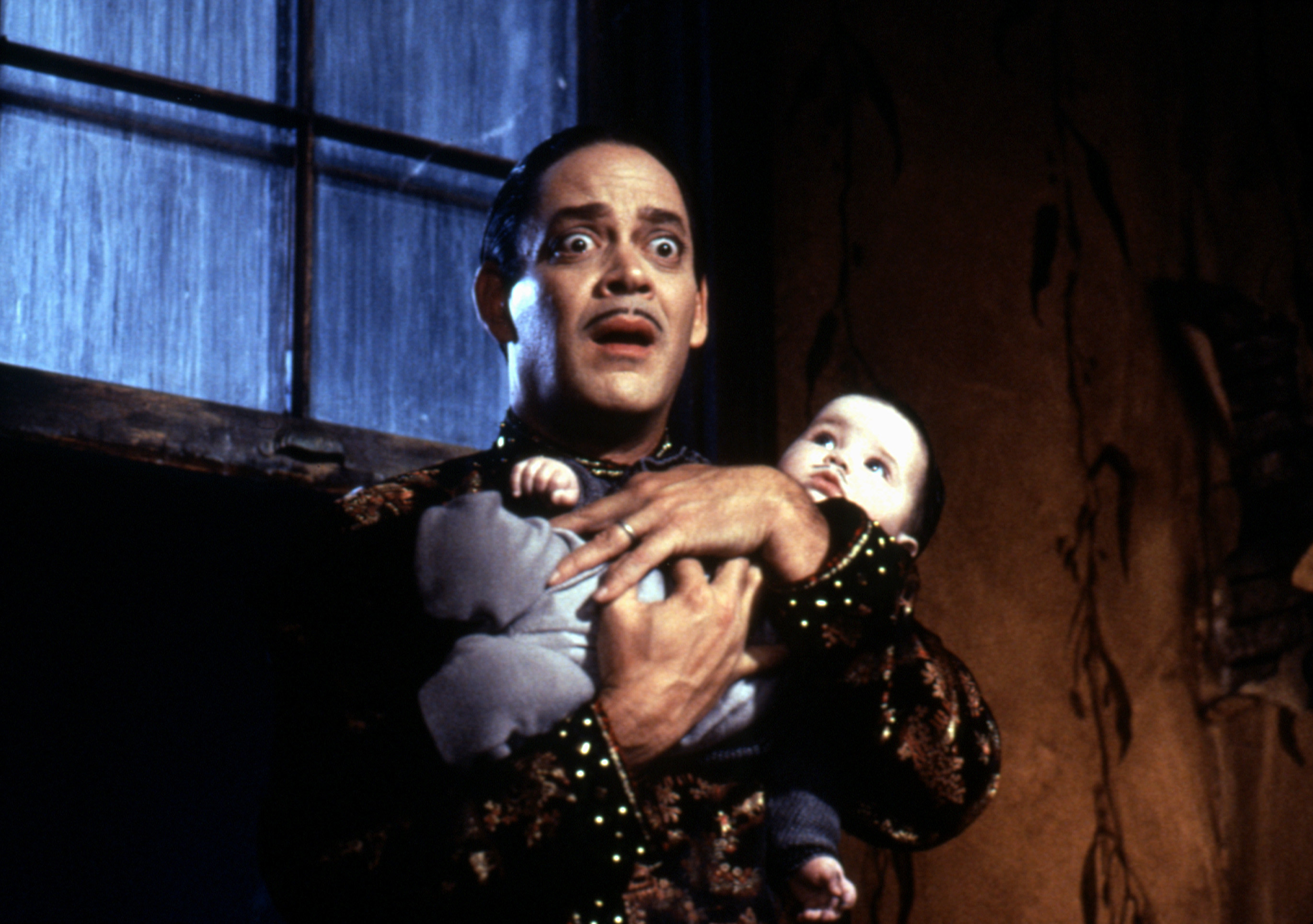 Gomez holds the baby, looking terrified