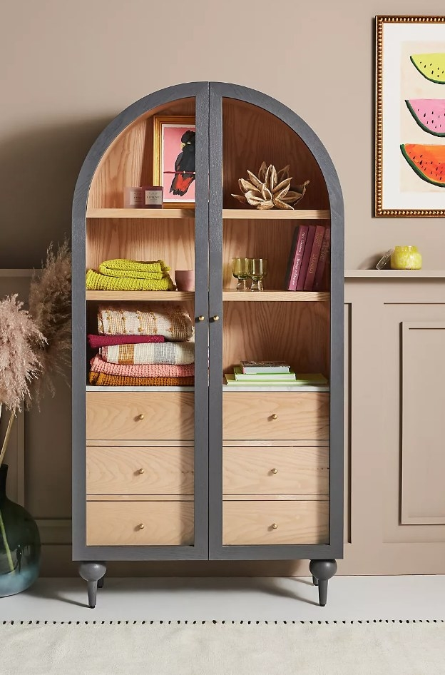 A wooden storage cabinet with glass doors and slate blue wood finishes