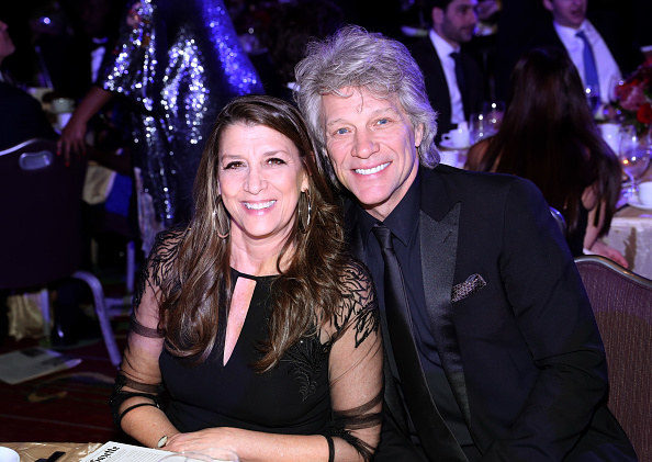 Dorothea and Jon smiling and sitting together at a formal event