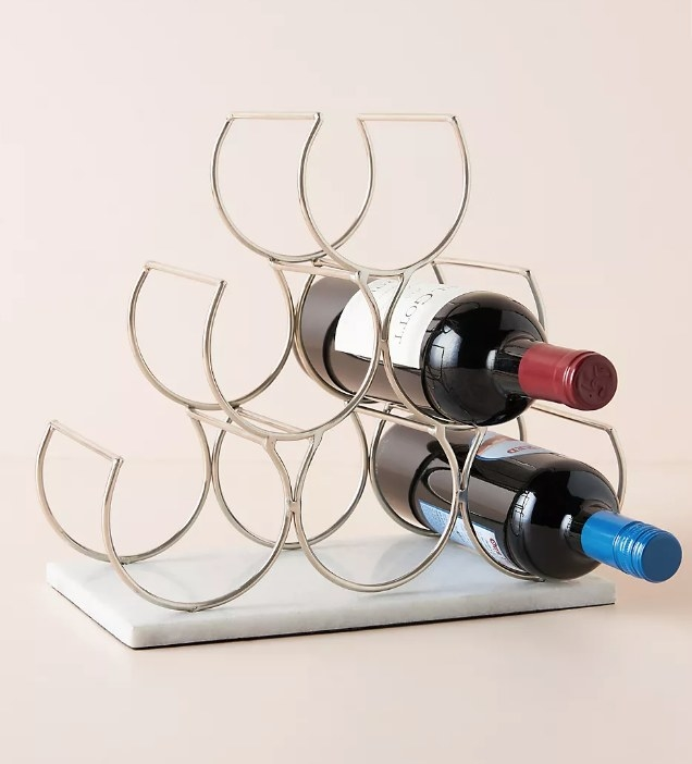 A wine rack that holds six bottles with a marble base