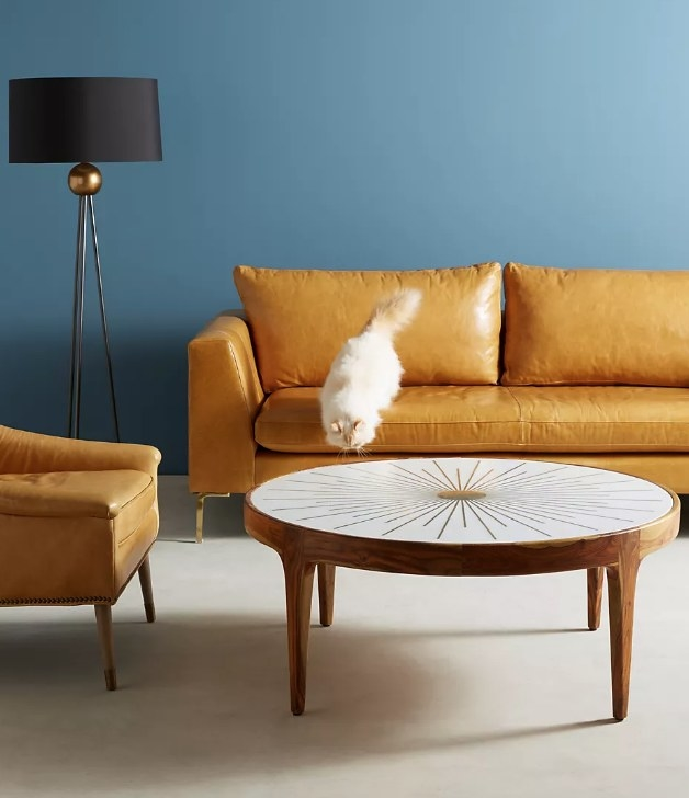 A round, wooden table with a marble top with a gold sunburst accent
