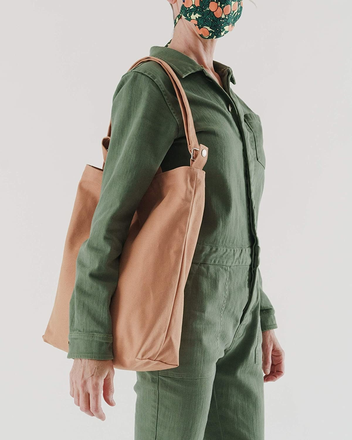 model carrying the adobe colored baggu tote from their shoulder
