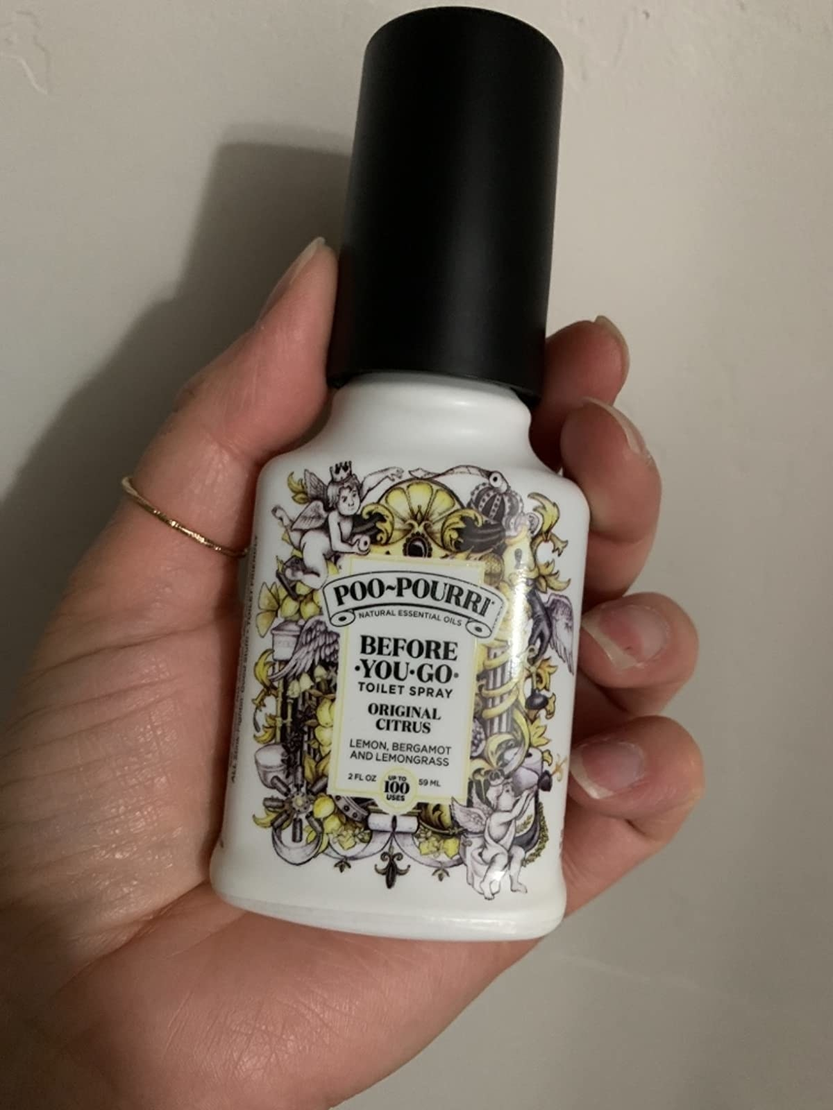 image of a reviewer's hand holding the 2 oz bottle of citrus poo-pourri