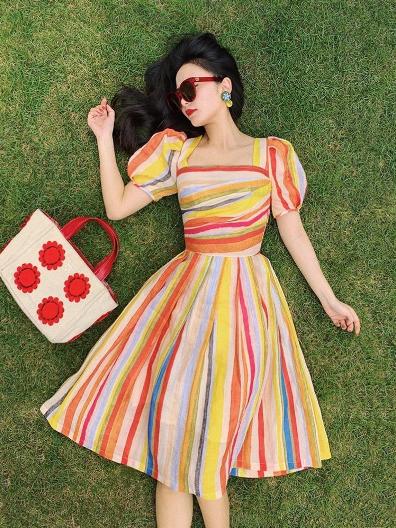 model wearing an A-line flared midi-dress with short puffy sleeves and stripes the color of pastel colors and bright colors