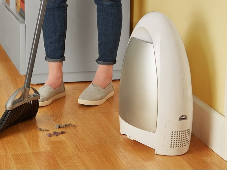 Model is sweeping dust into the white touchless vacuum